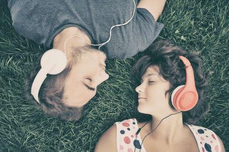 personas escuchando: Pares que escuchan la música en los auriculares