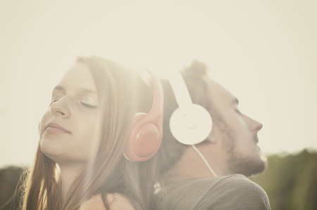 woman listening to music: Boy and girll listening to music on headphones Stock Photo