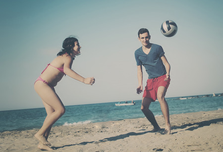 boardshorts: Couple playing volleyball on the beach