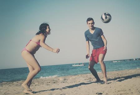 niño sin camisa: Pares que juegan a voleibol en la playa