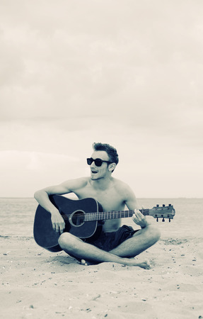 boy playing guitar: Boy playing guitar on the beach