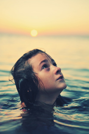 pureness: Young girl in red dress standing in sea at sunset Stock Photo
