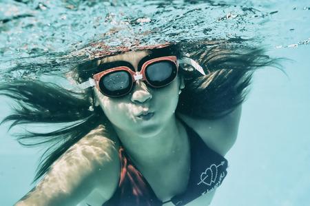 swimming underwater: Little girl swimming underwater in sea Stock Photo