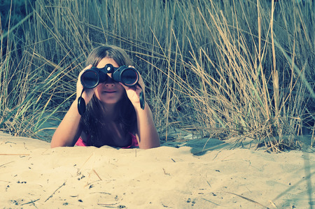 Young girl looking through binocular, low angle view photo