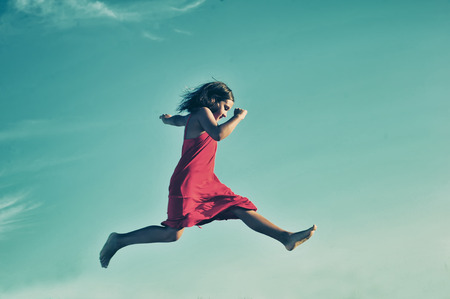 pureness: Young girl in red dress jumping on blue sky