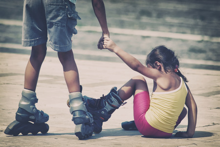 roller blade: Little boy and girl skating in the park Stock Photo