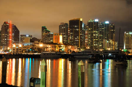 View of the San Diego skyline at night with water reflections.