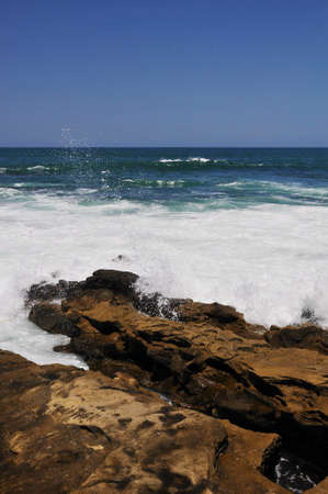 churning: View of the foamy churning surf as it hits the rocky shoreline at La Jolla, California. Stock Photo