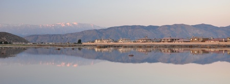 reflect: Residential homes and distant hills reflect in a large pond in Hemet, California.