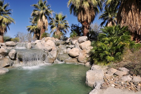 Water falls into a small pond at a park in Palm Desert, California  photo