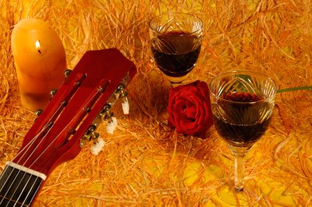 guitar, rose, wine on a straw background photo