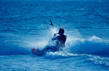 exhilaration: kite surfing, silhouette of sportsmen on blue Stock Photo