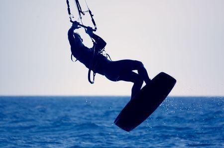 kiteboarding: kite surfing, silhouette of sportsmen on blue Stock Photo