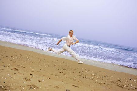 beautiful mature women running on a beach of sea photo