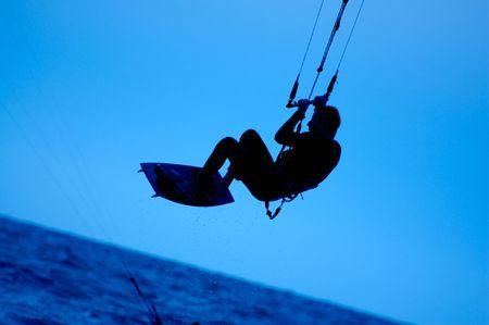 kite surfing, silhouette of sportsmen on blue photo