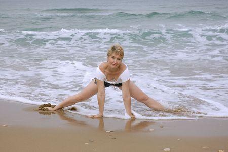 fitness of a beautiful mature women on a beach of sea photo