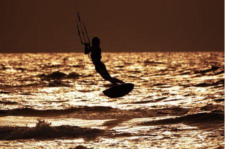 silhouette of flying kitesurfer  photo