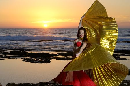 dancing girl ?in goldish dress on a sea coast photo