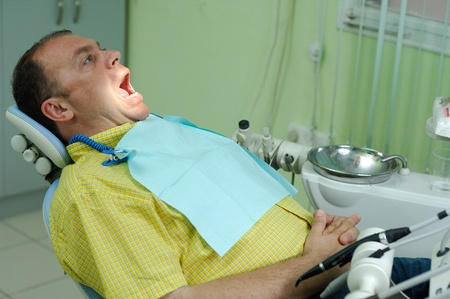 patient with the opened mouth in chair of dentist photo