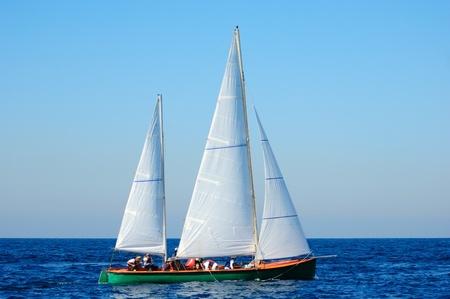 jib: Racing yacht in the mediterranean sea on blue sky background.