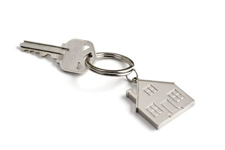 A metal key with a little house key ring on a white background Stock Photo