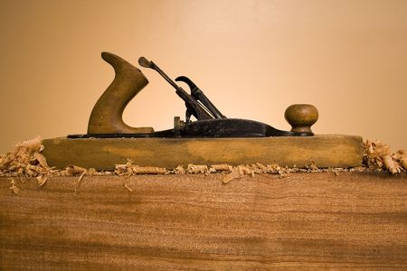 An old wood plane hand tool on a wooden block with wood shavings and saw dust. Stock Photo