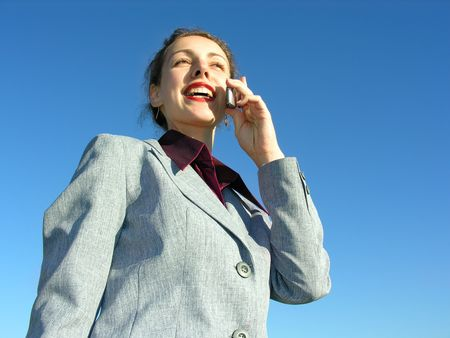 businesswoman with phone on blue sky from down view Stock Photo