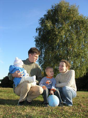 Family of four on grass blue sky autumn