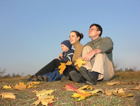 family sit with autumn leaves photo