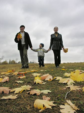 walking family with autumn leaves and clouds photo