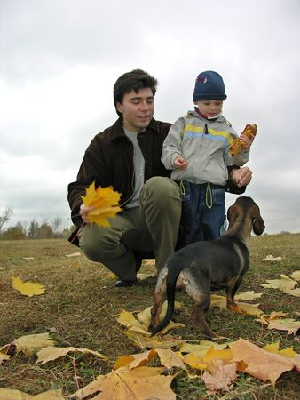 father with son and dog on autumn leaves