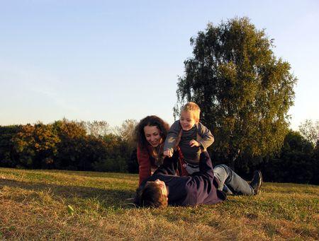 the glade: family plays autumn on sundown on glade Stock Photo