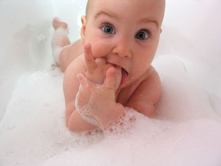 baby in bath. hand in mouth photo