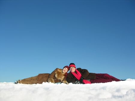 couples lies on snow photo