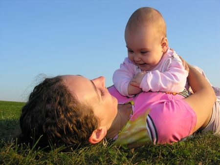 mother with baby on sunset lie Stock Photo