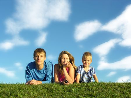 family on herb under blue sky with clouds Stock Photo