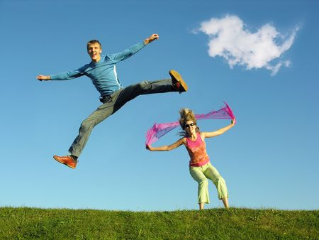 couple jump under cloud
