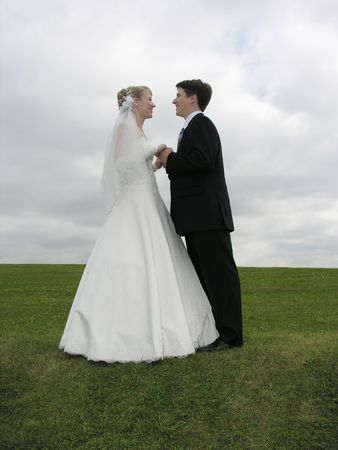 wedding face to face on grass and clouds photo