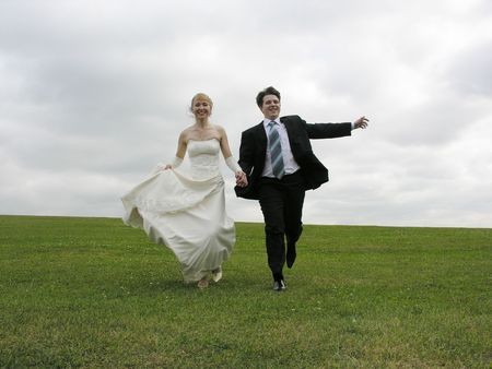 bride and groom running on meadow Stock Photo - 423115