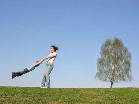 rotate: mother rotate son on meadow Stock Photo