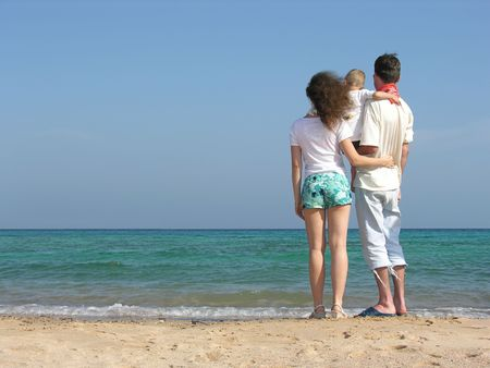 back family of thre on beach