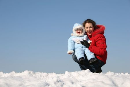 smile mother sit with baby. winter photo