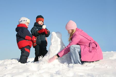 mother with children play on snow photo