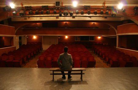 settle back: man alone on theater scene Stock Photo