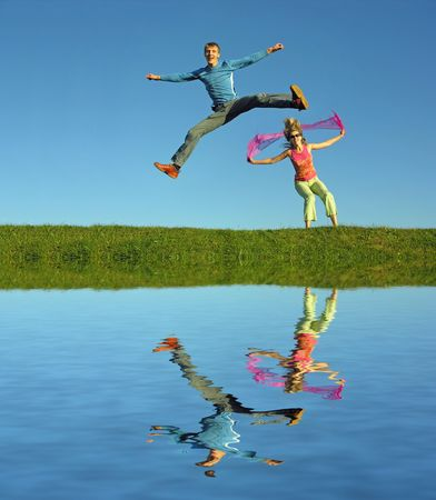 full strenght: couples jump on grass and water Stock Photo