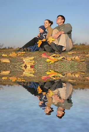 family sit with autumn leaves and water