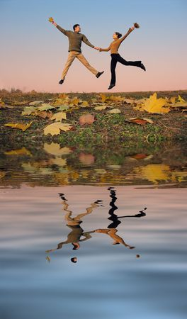 full strenght: jump couple. autumn leaves. sunset water