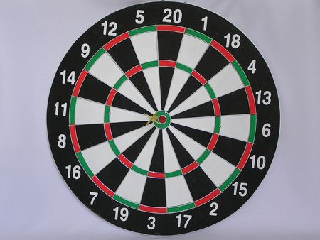 On a photo game of a darts. The target of different colors is divided  into sector. In the center darts. The photo is made in Ukraine.