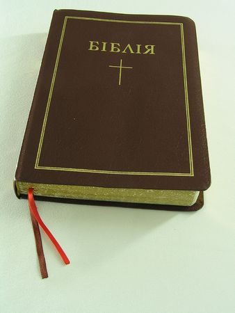 imposition: On a photo the Sacred Bible. A cover of brown color. On a cover an inscription in the Ukrainian language and a cross      Stock Photo