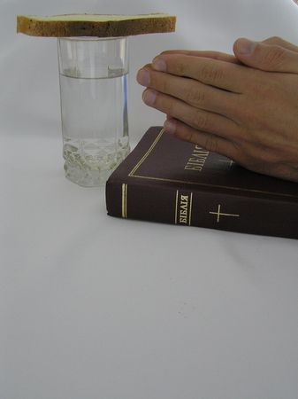 abstention: On a photo on a white background a glass with water, and bread, the Bible and hands combined in a pray. The photo is made in Ukraine. A symbol of gratitude to the God for I peep.
